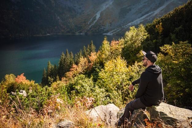 Man toeristische ontspannen op de top van een heuvel, kijken naar een prachtig landschap van bergen en meer.