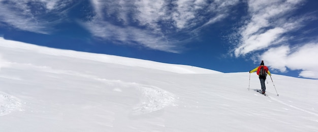 Man toerskiën klimmen met sneeuw bedekte berg onder blauwe en bewolkte hemel
