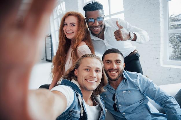Man toont duim. vrolijke jonge vrienden die selfies op bank en wit binnenland nemen