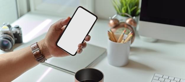Man toont mock-up smartphonescherm zittend aan de werktafel met kantoorbenodigdheden
