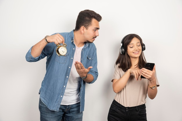 Man toont tijd aan ongeïnteresseerde vrouw die naar een lied luistert.