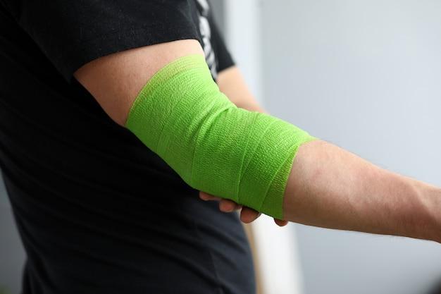 Man toont zich uitrekken op arm met elastische bandage.