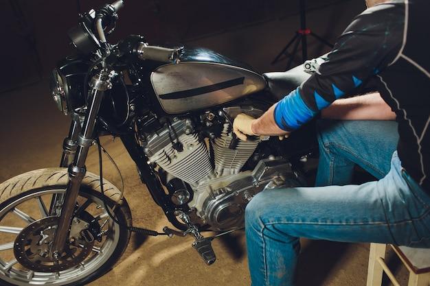 Man tot vaststelling van de fiets. zekere jonge mens die motorfiets herstelt dichtbij zijn garage.