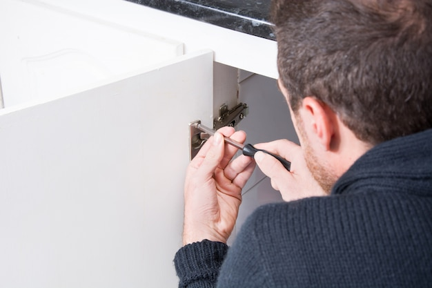 Man tot vaststelling van een kast met een schroevendraaier