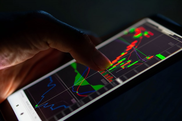 Man touch kandelaar grafiek van beurs op smartphone