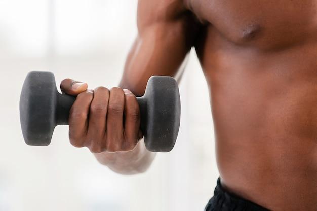 Man training met halters. bijgesneden afbeelding van afrikaanse man die traint met halters