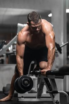 Man traint in de sportschool atletische man traint met halters, pompen zijn biceps