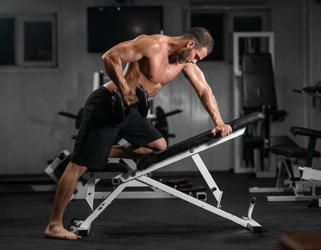 Man traint in de sportschool. atletische man traint met halters, pompen zijn biceps