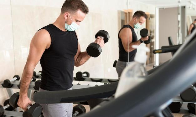 Man traint in de sportschool terwijl hij een medisch masker draagt