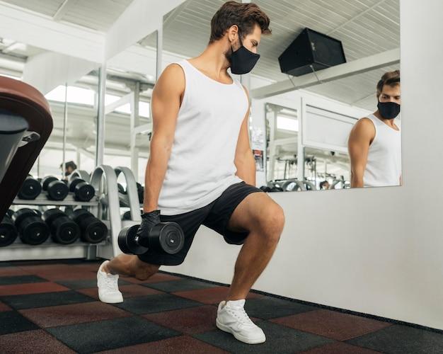 Man traint in de sportschool terwijl hij in de spiegel kijkt