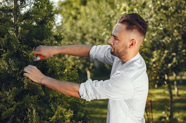 Man trimmen tak van borstel. guy werkt in een achtertuin.