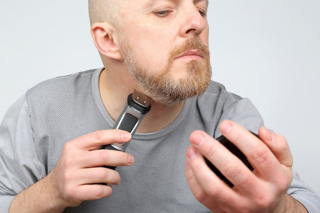 Man trimmer corrigeert zijn baard