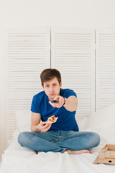 Man tv kijken zittend op het bed en pizza eten