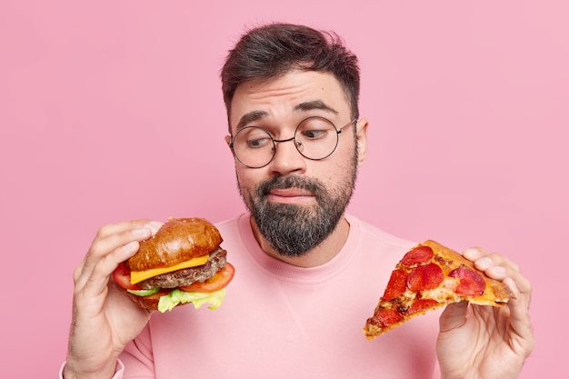 Man twijfelt of hij hamburger of pizza moet eten, eet liever junkfood draagt een ronde bril en een trui