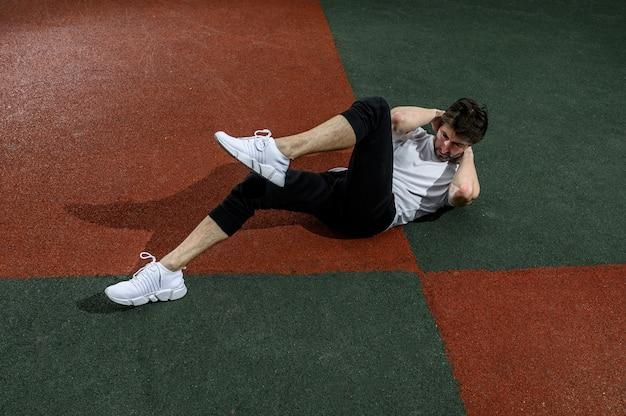 Man twist abs oefening met verhoogde benen doen. foto van jonge man training langs buiten in de stad