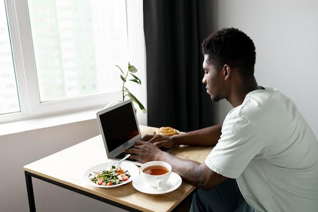 Man typt op laptop thuis medium shot
