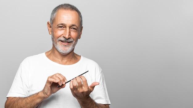 Man uit een gemiddeld schot die zijn nagels vijlt