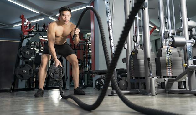 Man uit te werken met touwen van de strijd op sportschool