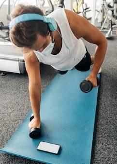 Man uit te werken op de mat in de sportschool tijdens het kijken naar smartphone