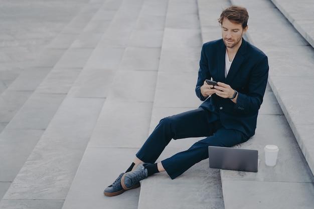 Man uitvoerende werknemer gebruikt mobiele telefoon om te chatten, werkt op afstand en maakt project via laptopcomputer