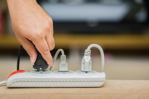 Man unplugged plug om energie te besparen