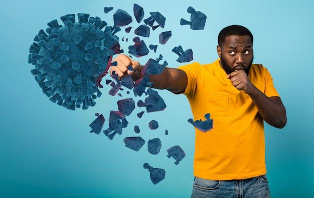 Man valt met een klap het coronavirus aan. blauwe muur
