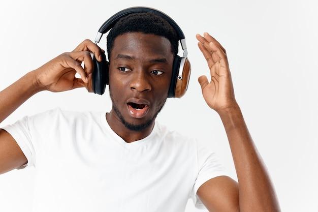 Man van afrikaanse uitstraling met koptelefoon luisteren naar muziek technologie moderne stijl