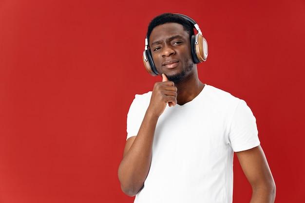 Man van afrikaanse verschijning in hoofdtelefoons die witte t-shirtmuziek geïsoleerde achtergrond dragen