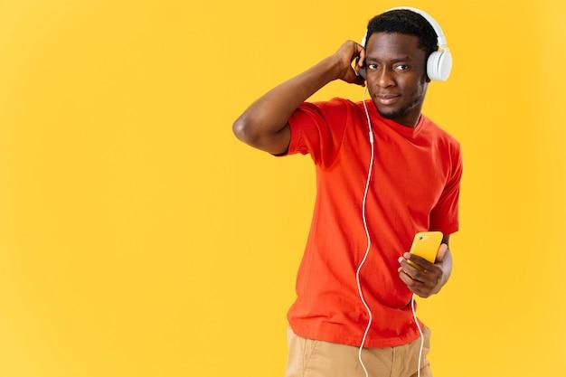 Man van afrikaanse verschijning in koptelefoon met een telefoon luistert naar muziek gele achtergrond