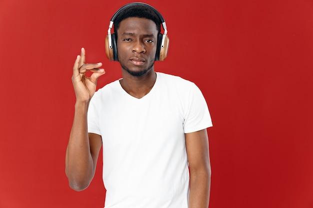Man van afrikaanse verschijning in koptelefoon toont vingertechnologie