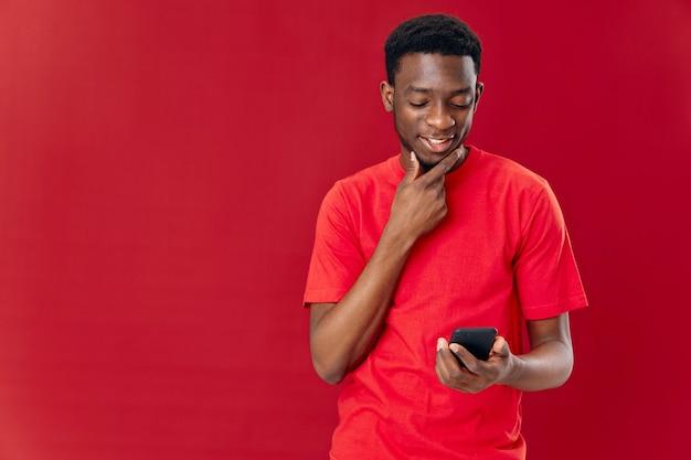 Man van afrikaanse verschijning met een telefoon in zijn handen glimlachtechnologie