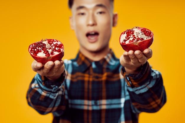 Man van aziatische verschijning in een geruit hemd met granaatappels in zijn handen fruit gele achtergrond