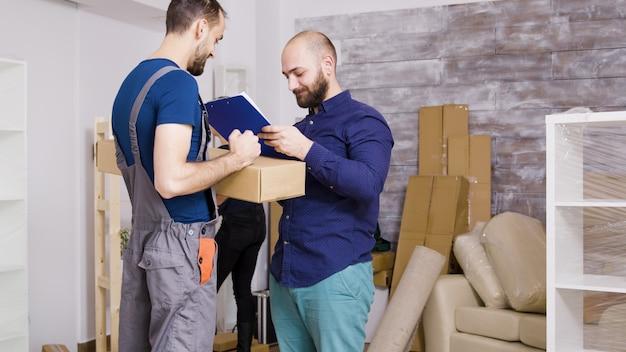 Man van bezorgservice arriveert met dozen en te ondertekenen documenten. mooie jonge paar verhuizen naar binnen.