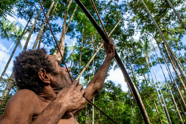 Man van de korowai-stam schiet een boog in het bos.