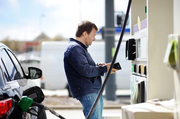 Man van de middenleeftijdsmens het vullen benzinebrandstof in auto
