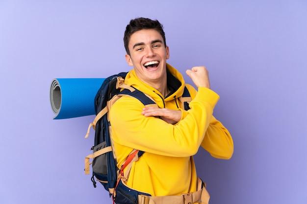 Man van de tiener de kaukasische bergbeklimmer met een grote die rugzak op purple wordt geïsoleerd die sterk gebaar maken