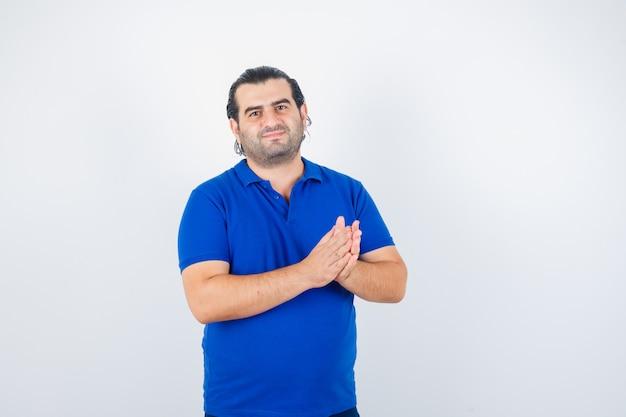 Man van middelbare leeftijd applaudisseren in blauw t-shirt en op zoek gelukkig, vooraanzicht.