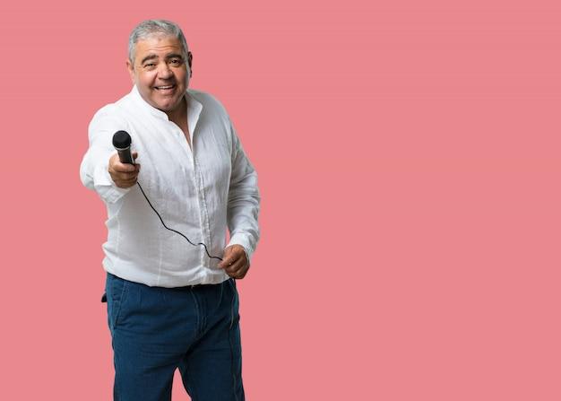 Man van middelbare leeftijd, blij en gemotiveerd, een lied zingen met een microfoon, een evenement presenteren of een feestje vieren, geniet van het moment