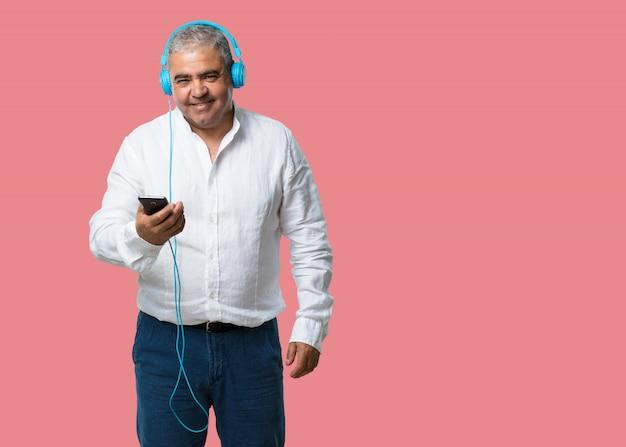 Man van middelbare leeftijd blij en leuk, luisteren naar muziek, moderne koptelefoon, blij gevoel het geluid en het ritme