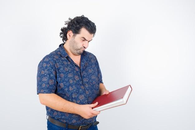 Man van middelbare leeftijd boek in overhemd kijken en nadenkend kijken. vooraanzicht.