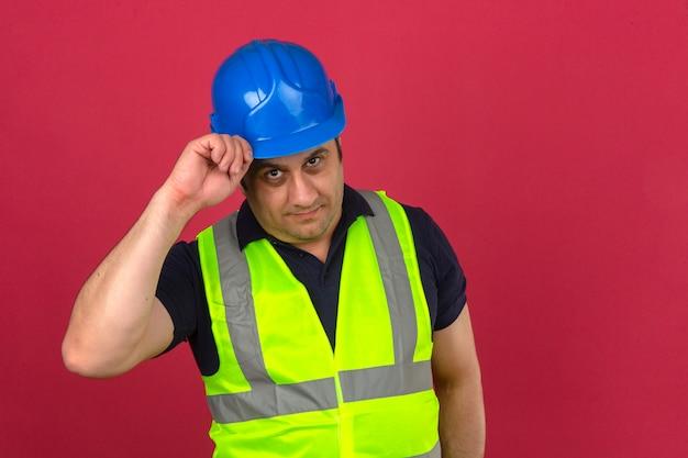Man van middelbare leeftijd bouw geel vest dragen en veiligheidshelm groet gebaar maken door zijn helm met een glimlach op het gezicht over geïsoleerde roze muur aan te raken