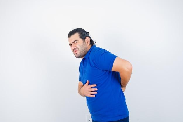 Man van middelbare leeftijd die aan rugpijn in blauw t-shirt lijdt en onwel, vooraanzicht kijkt.