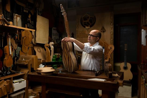 Man van middelbare leeftijd die alleen instrumenten maakt in zijn werkplaats
