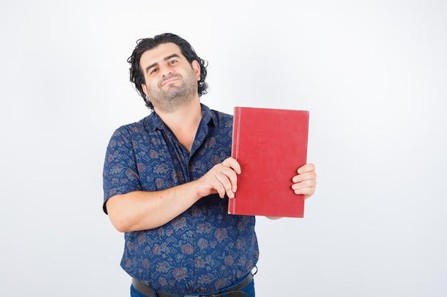 Man van middelbare leeftijd die boek in overhemd voorstelt en zelfverzekerd kijkt. vooraanzicht.