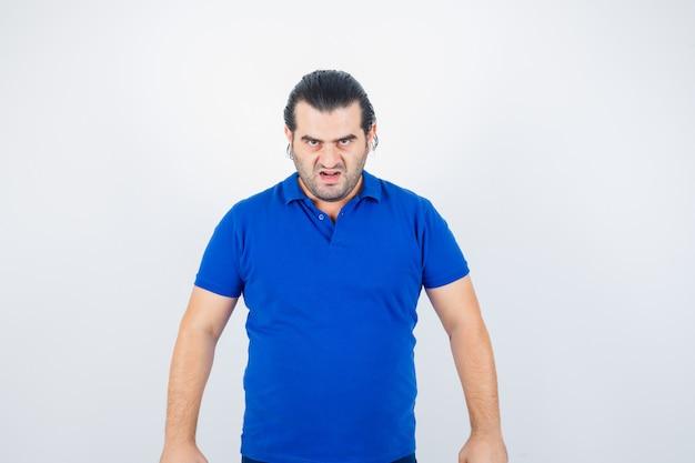 Man van middelbare leeftijd die camera in blauw t-shirt bekijkt en hatelijk kijkt. vooraanzicht.