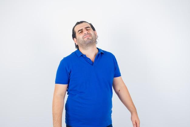 Man van middelbare leeftijd die camera in polot-shirt bekijkt en aarzelend, vooraanzicht kijkt.