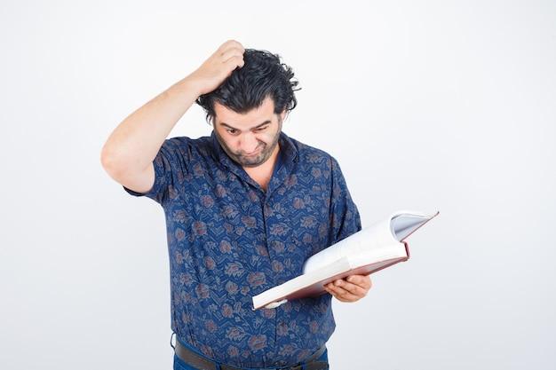 Man van middelbare leeftijd die door boek kijkt terwijl hoofd in overhemd krabt en nadenkend, vooraanzicht kijkt.