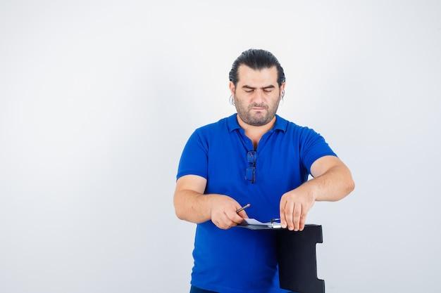 Man van middelbare leeftijd die door klembord kijkt terwijl de pagina in polot-shirt wordt omgeslagen en peinzend kijkt. vooraanzicht.