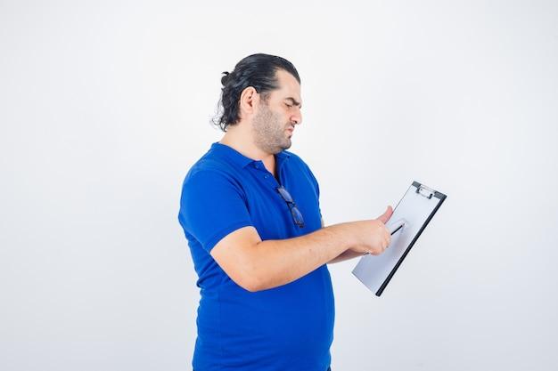 Man van middelbare leeftijd die door klembord kijkt terwijl hij potlood in polot-shirt vasthoudt en nadenkend, vooraanzicht kijkt.