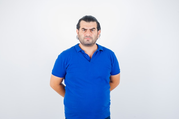 Man van middelbare leeftijd die handen achter rug in polot-shirt houdt en agressief, vooraanzicht kijkt.